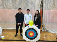 3 students with archery target after balloon challenge