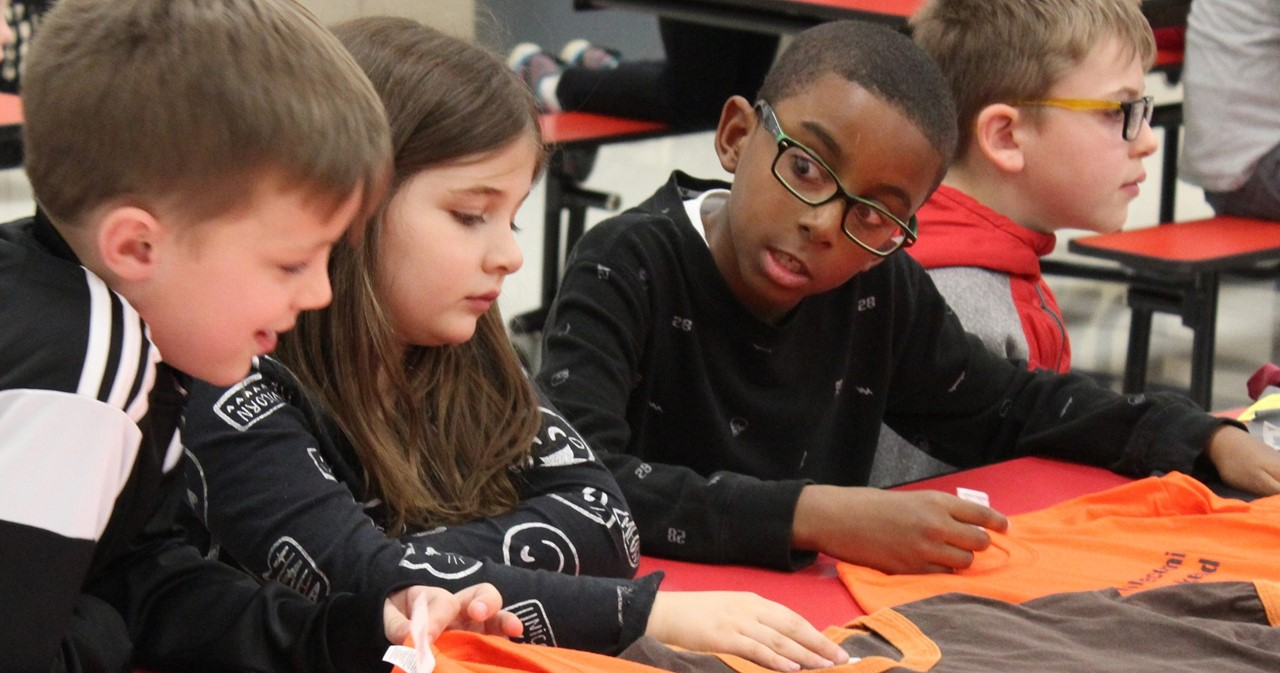 Four students at CES sitting at a table and working on a crafts project