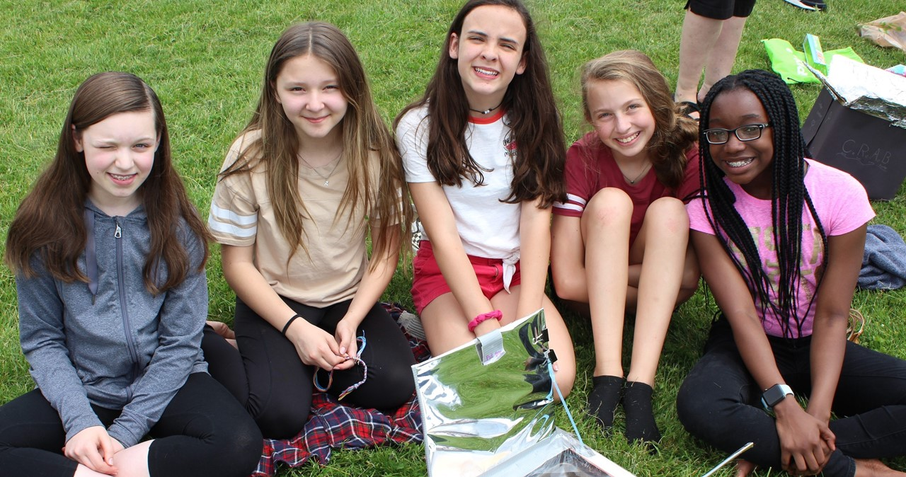 Five MS students outside on the lawn testing their solar cooker