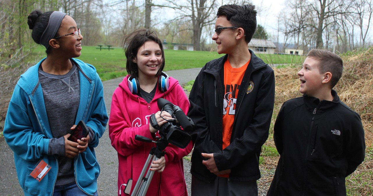 Four video club members with their equipment in the park