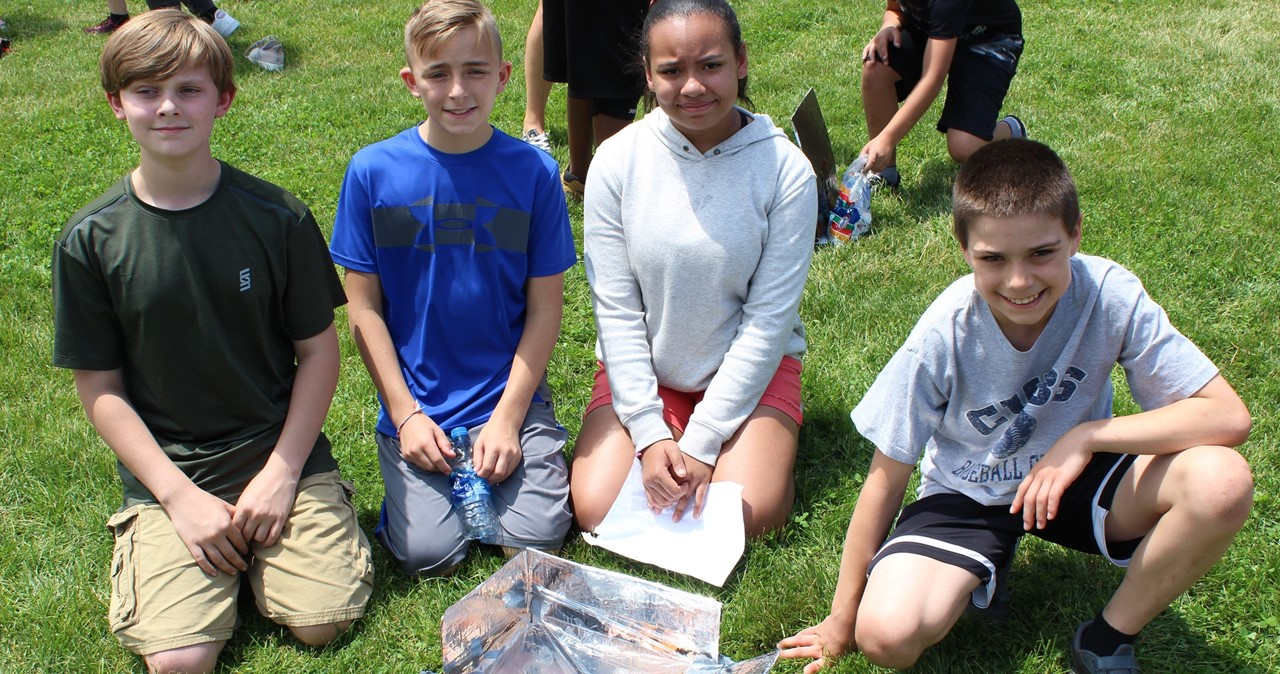 Four students on the lawn with their solar cooker