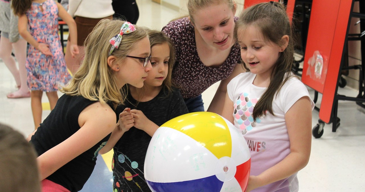 Three CES students speaking to a visiting RIT student while holding a beach ball