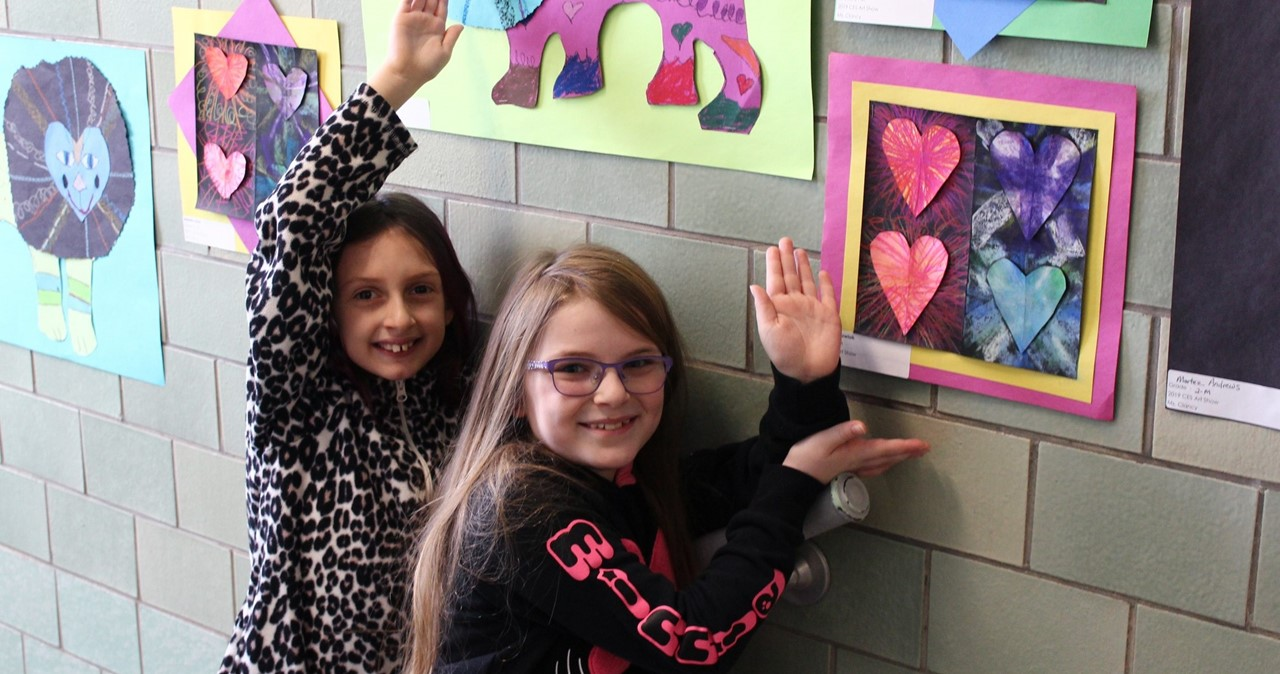 Two students pointing out their artwork