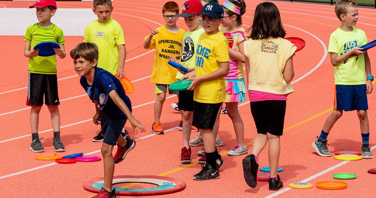 Group of students throwing frisbees on the track during FRS Field Days