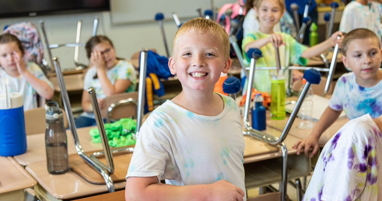 Smiling student with many other students in a classroom with chairs upside down on desks