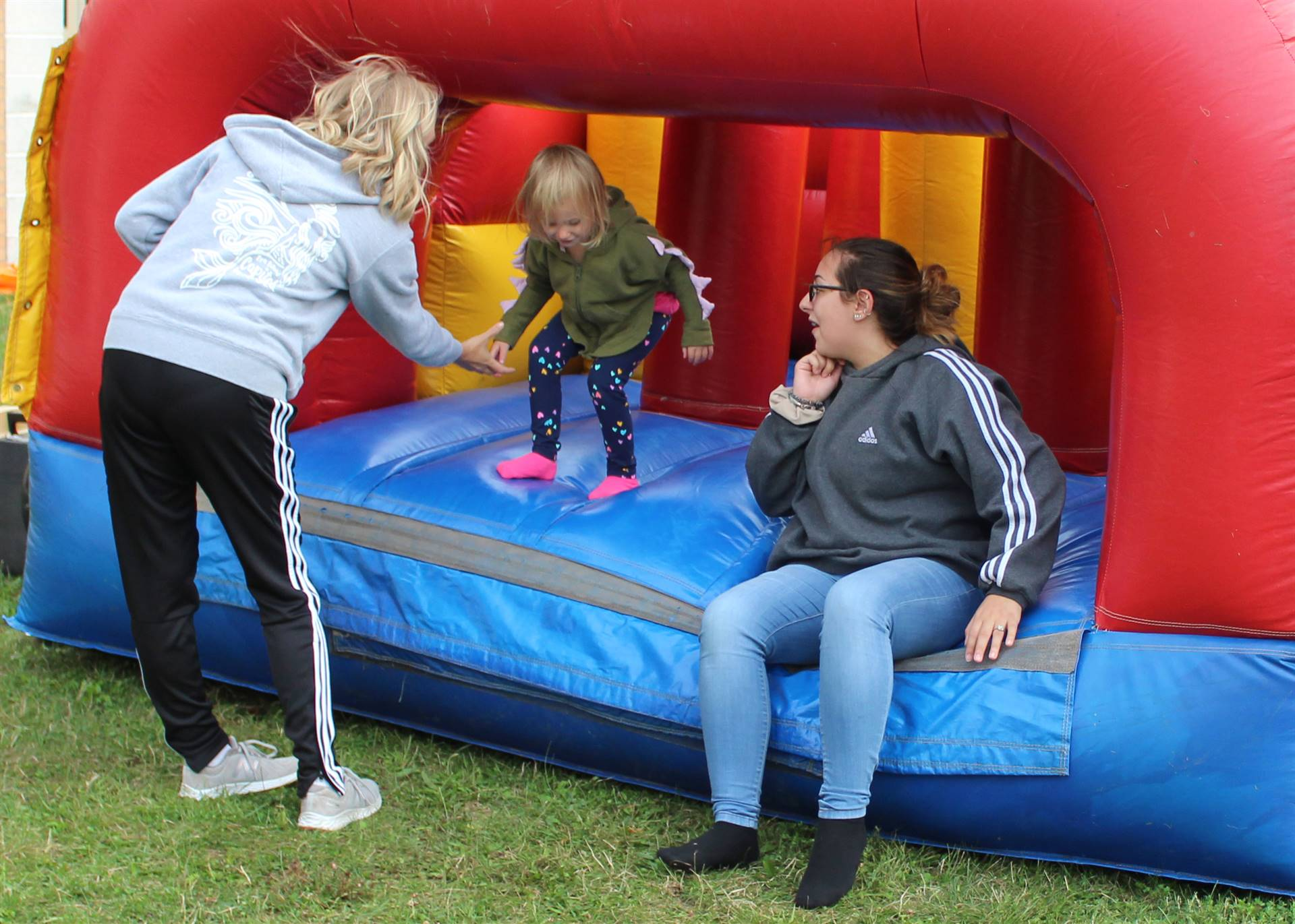 Two older students help a younger one navigate the bounce house