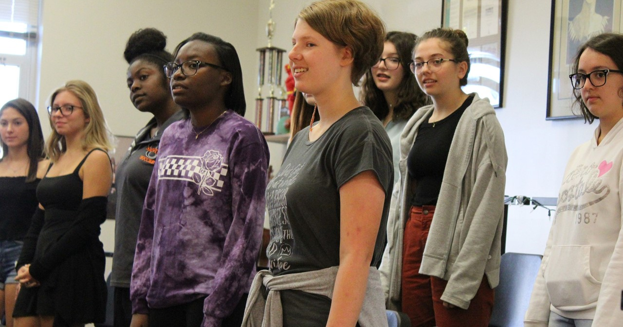 A group of high school vocalists begin practicing