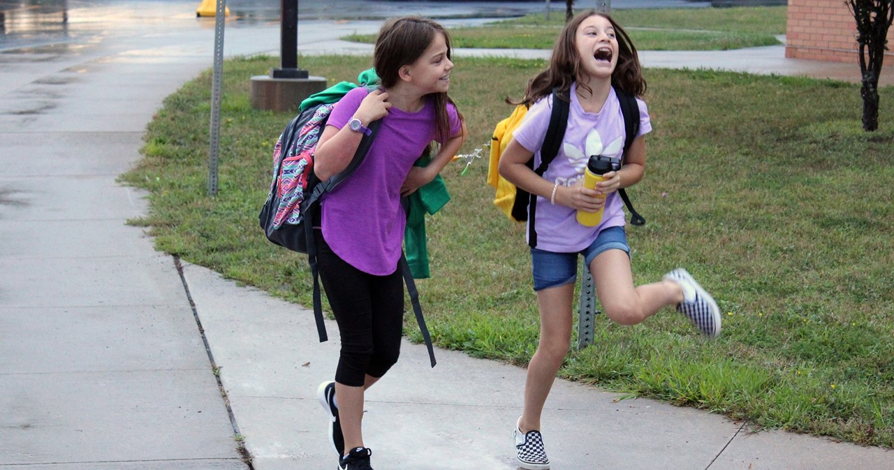 Two excited students laughing as they arrive for classes