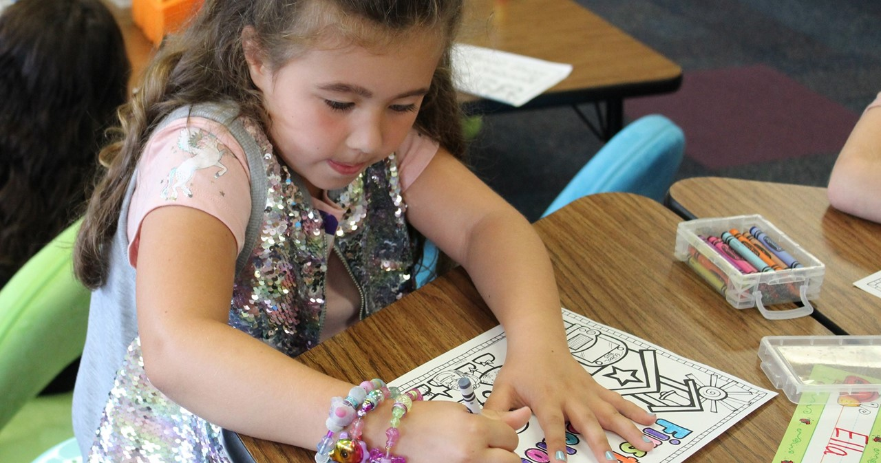 Student in sequined dress coloring