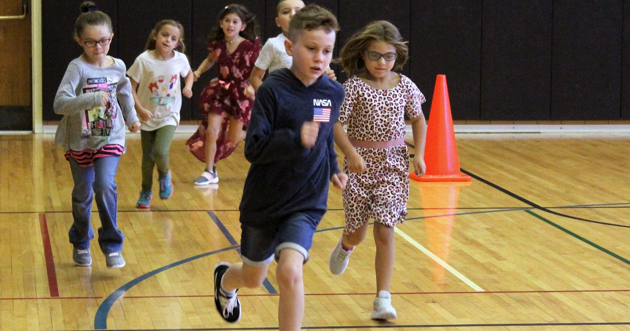 Group of students running in the gym