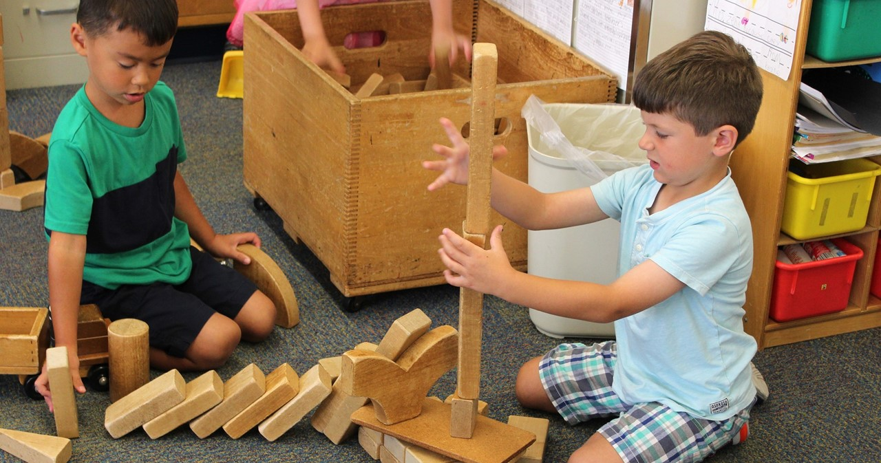 Two students sitting on the floor using building blocks