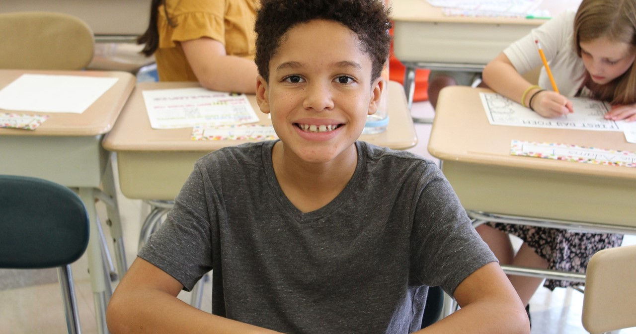 Student with great smile sitting at desk