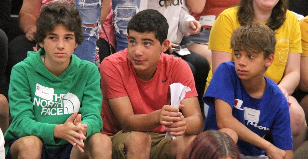 Three students wearing green, red and blue shirts