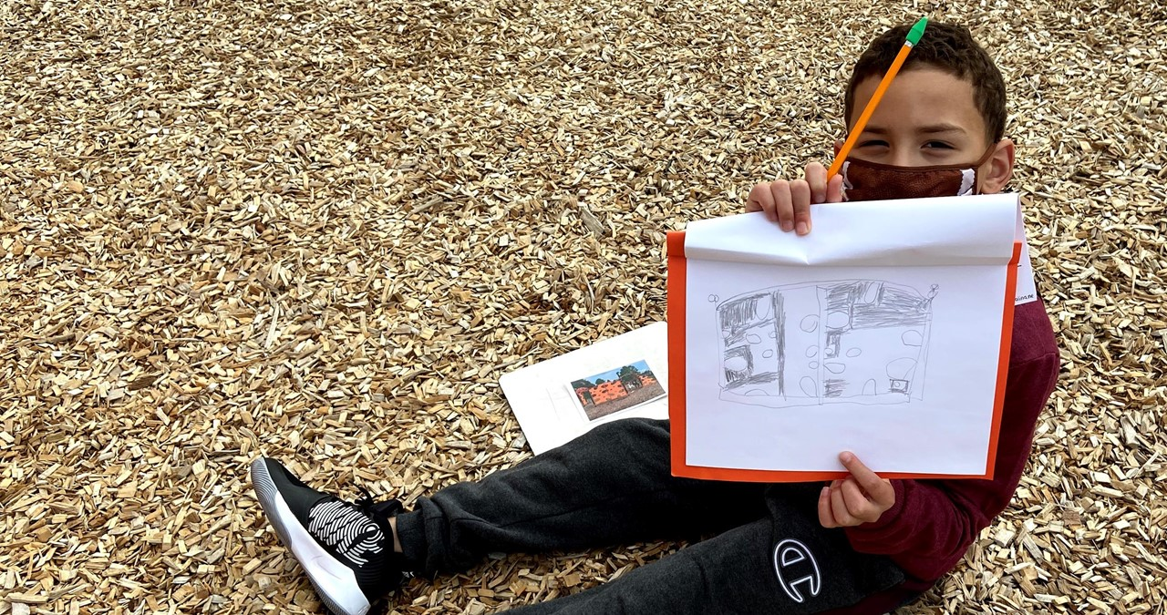 Student sitting on the ground displaying artwork