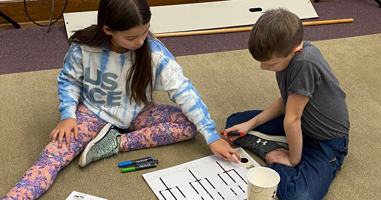 Two friends sitting on the floor working with Ozobots