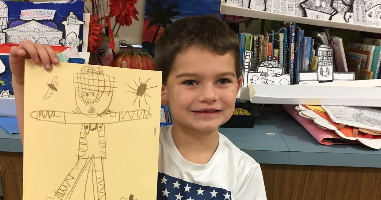 Smiling student holding artwork of scarecrow