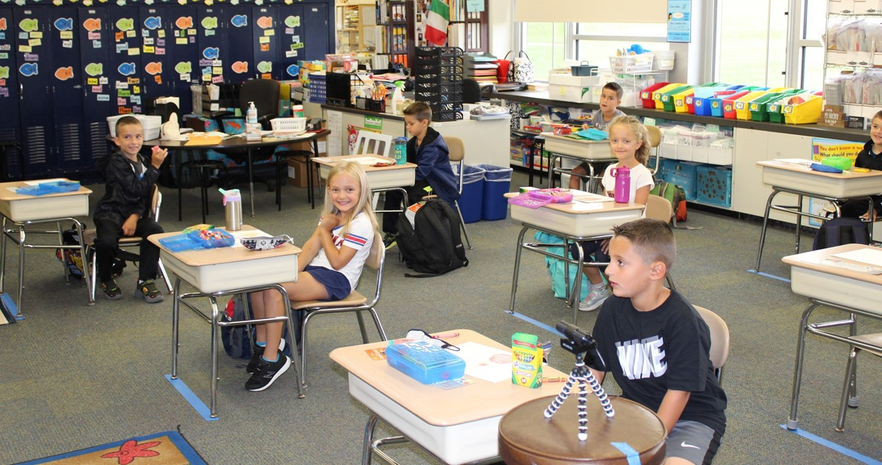 Socially distanced students sitting at desks in a classroom