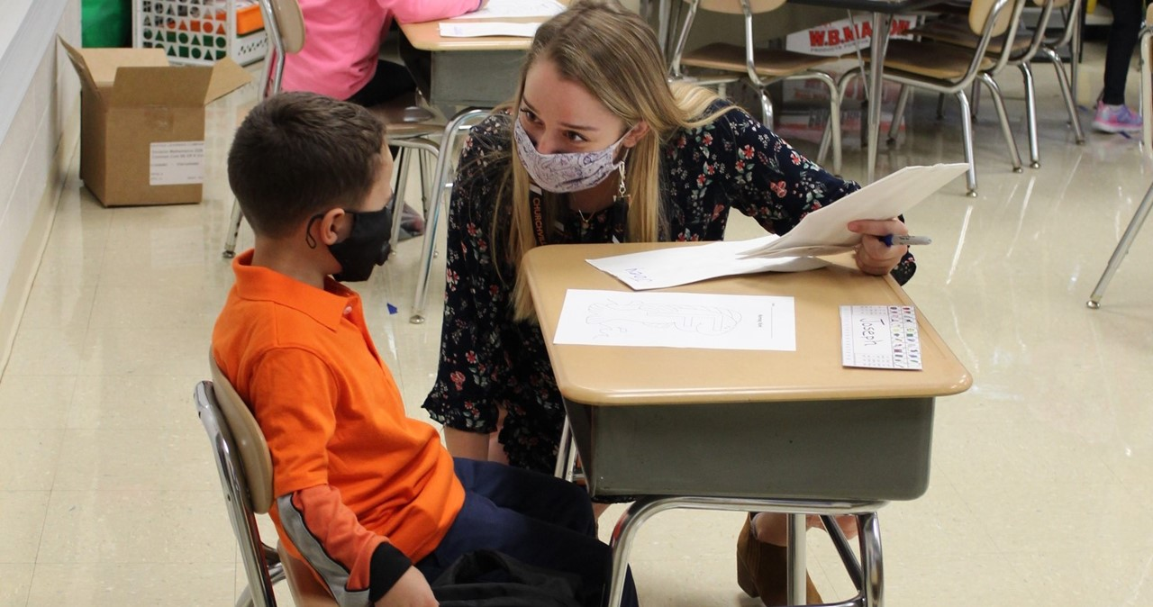 Student and teacher talking; both are wearing masks
