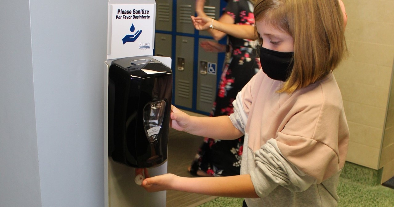 Masked student using a hand sanitizer station