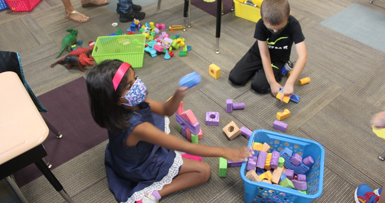 Students playing with brightly colored blocks