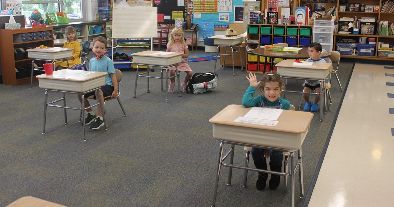 Smiling students sitting at their desks in a socially distanced classroom