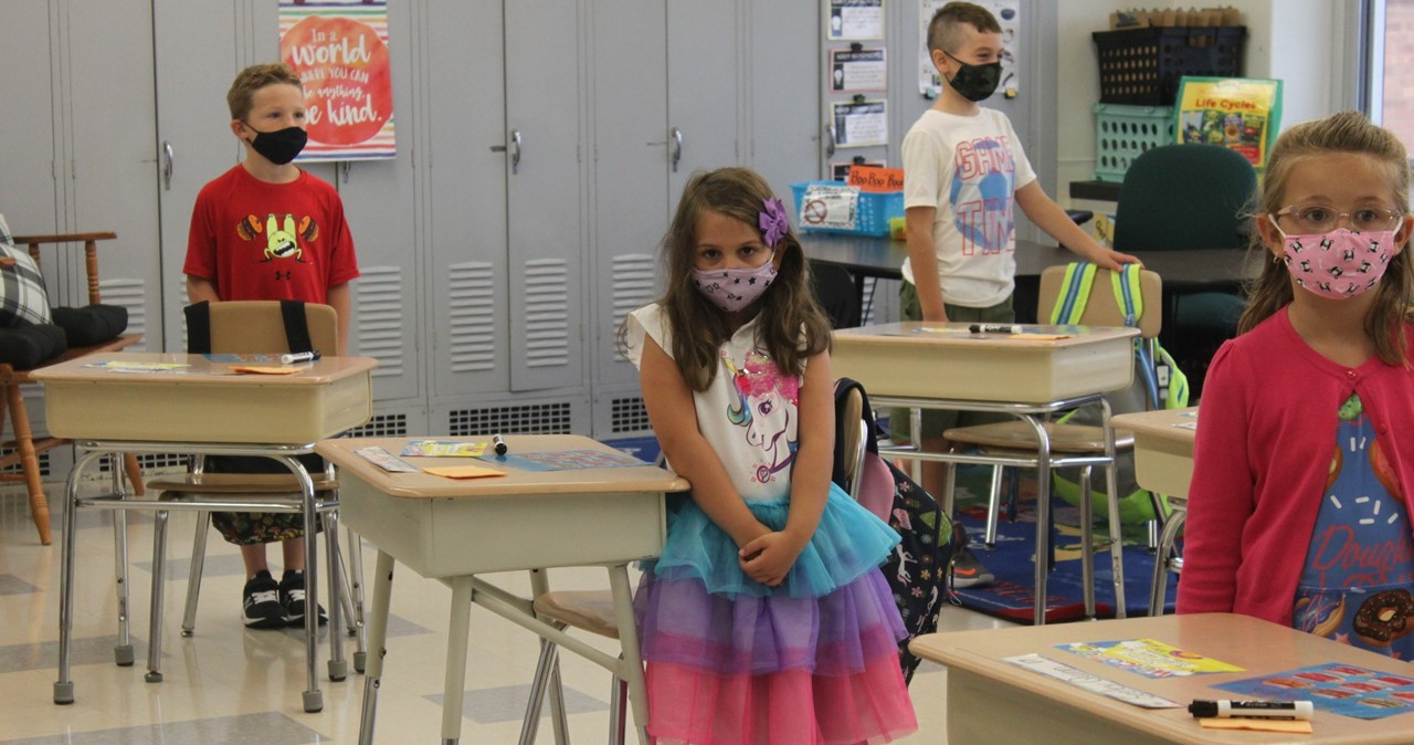 Students wearing masks and standing next to their desks