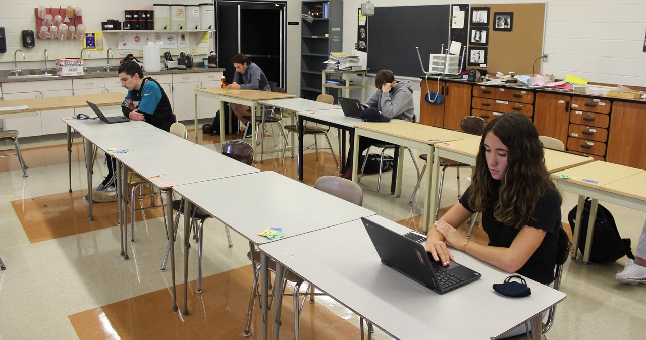 Socially distanced students working on laptops