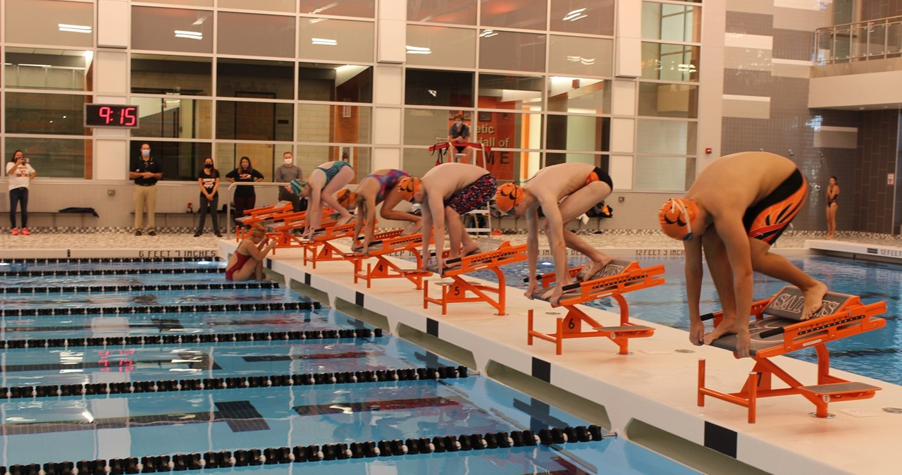 Line up of swimmers ready to dive into the new pool