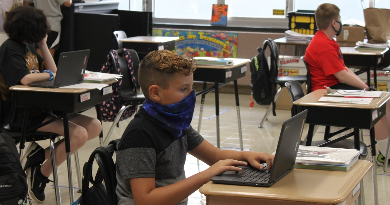 Student with mask working on laptop