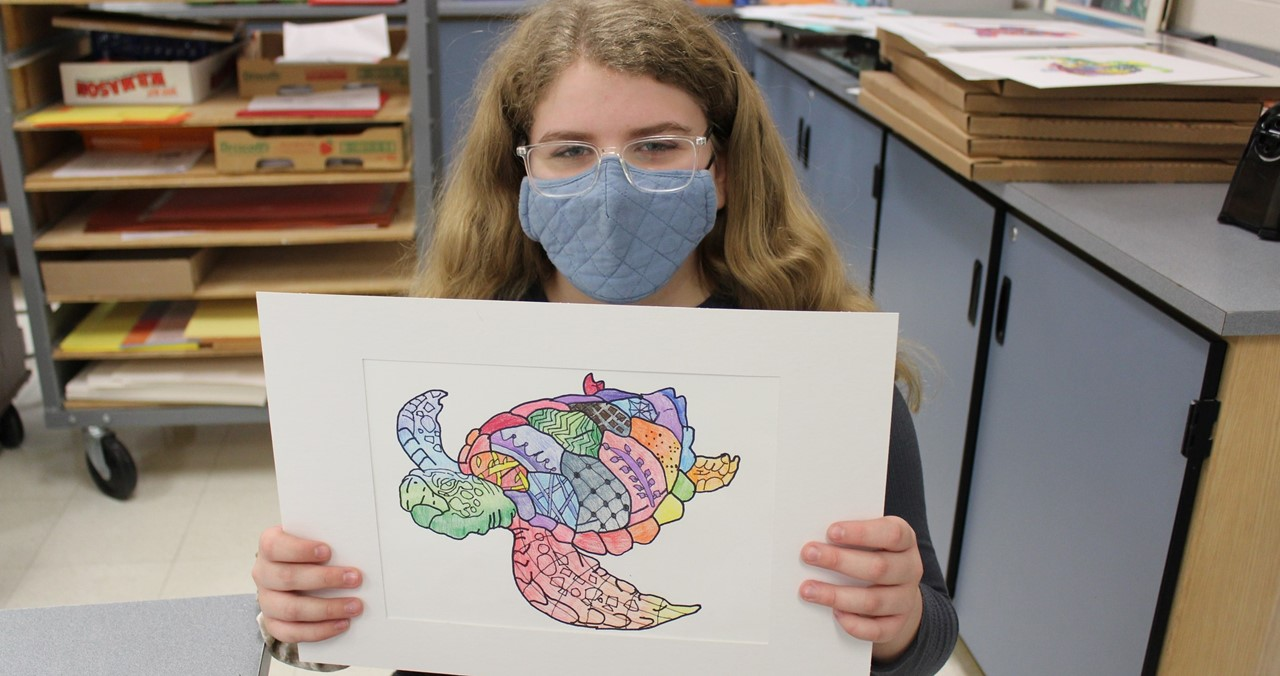 Middle school student holding turtle artwork