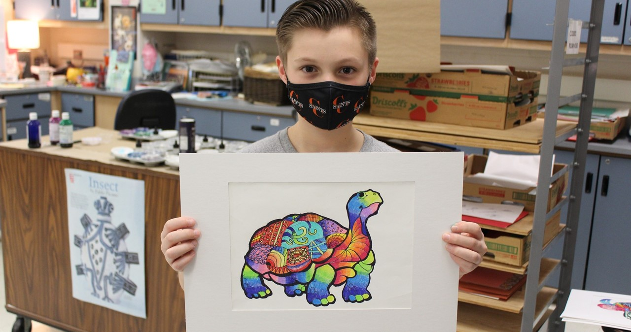 Middle school student wearing mask holding turtle artwork