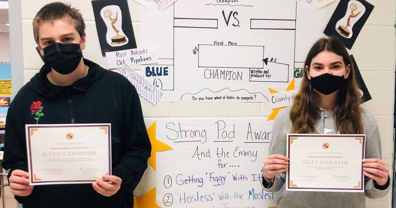 Two students wearing masks holding certificates for winning podcasts