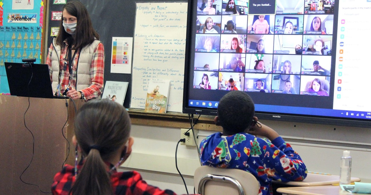 In-person students and remote students zooming in from home on a large screen