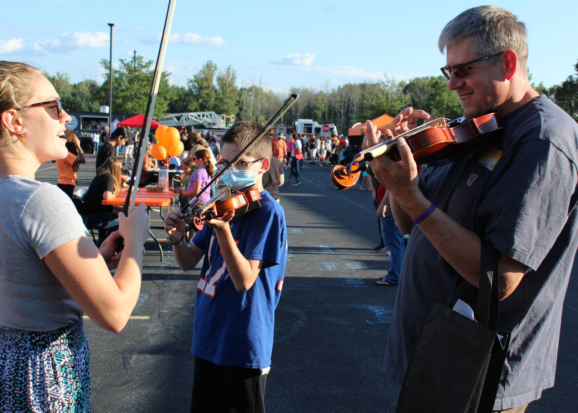 Music teacher demonstrating violins to student and parent