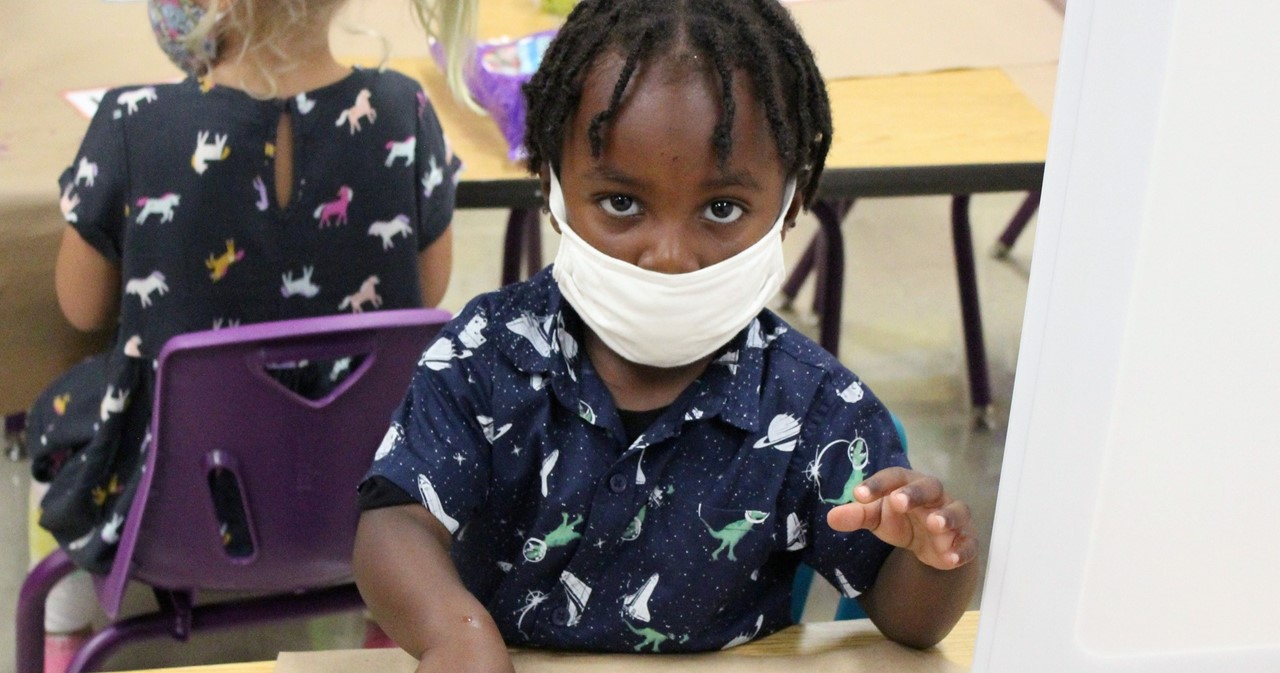 Pre-K student at a desk wearing a mask