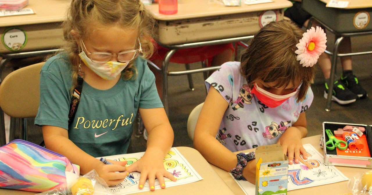 Two students coloring with crayons