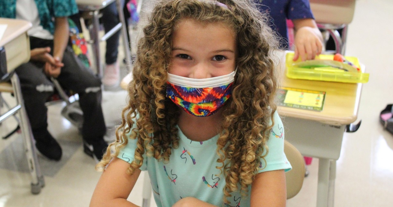 Student with curls and colorful face mask
