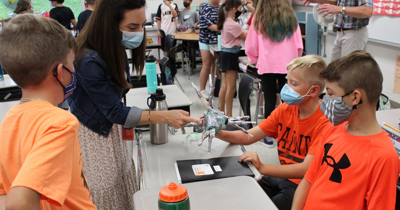 Students sharing their experiment with teacher