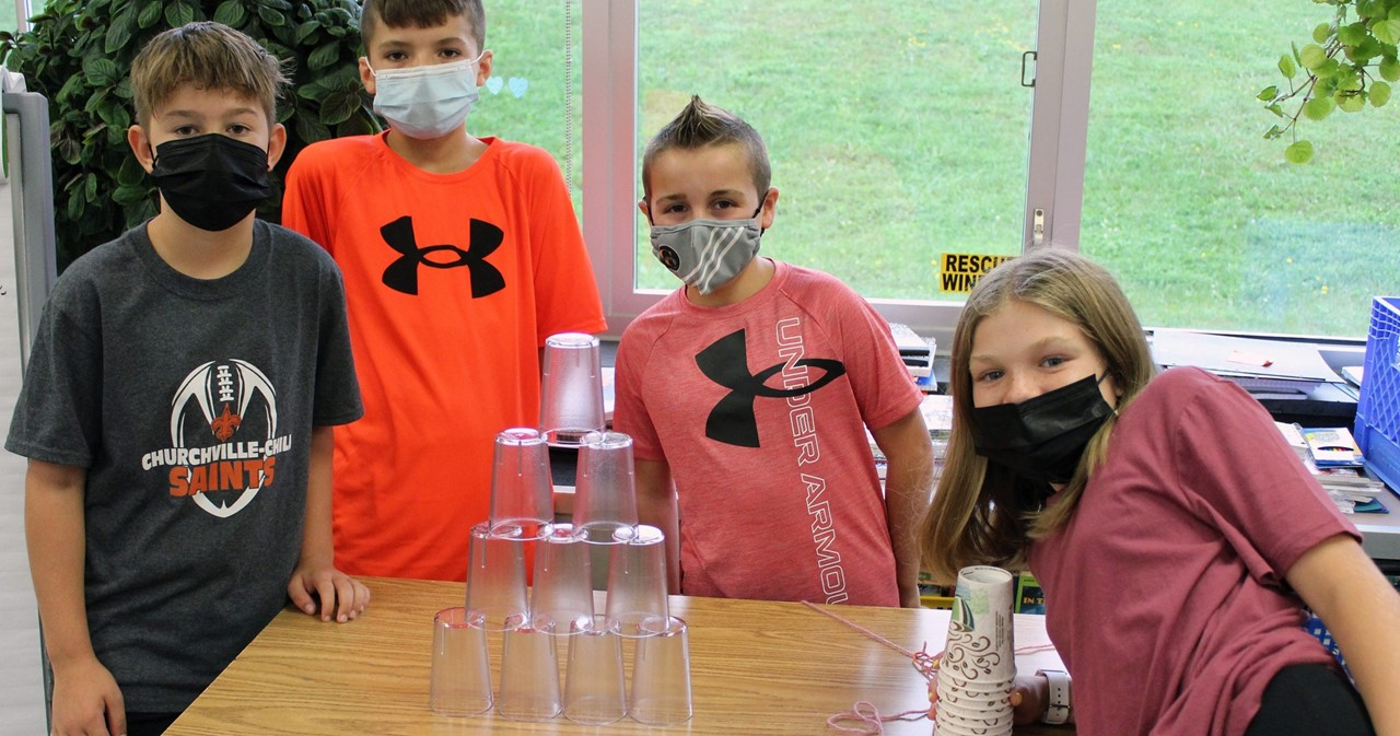 Four students who successfully built a pyramid from glasses
