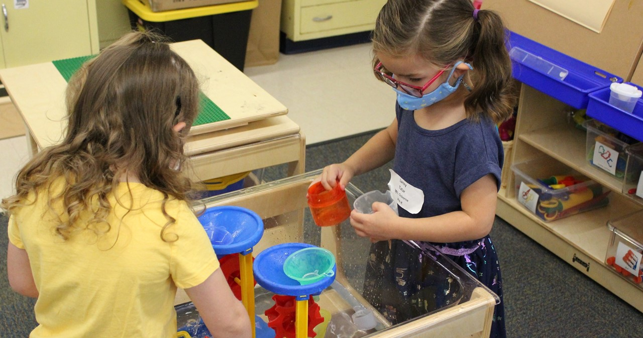 Two students playing together with a water toy