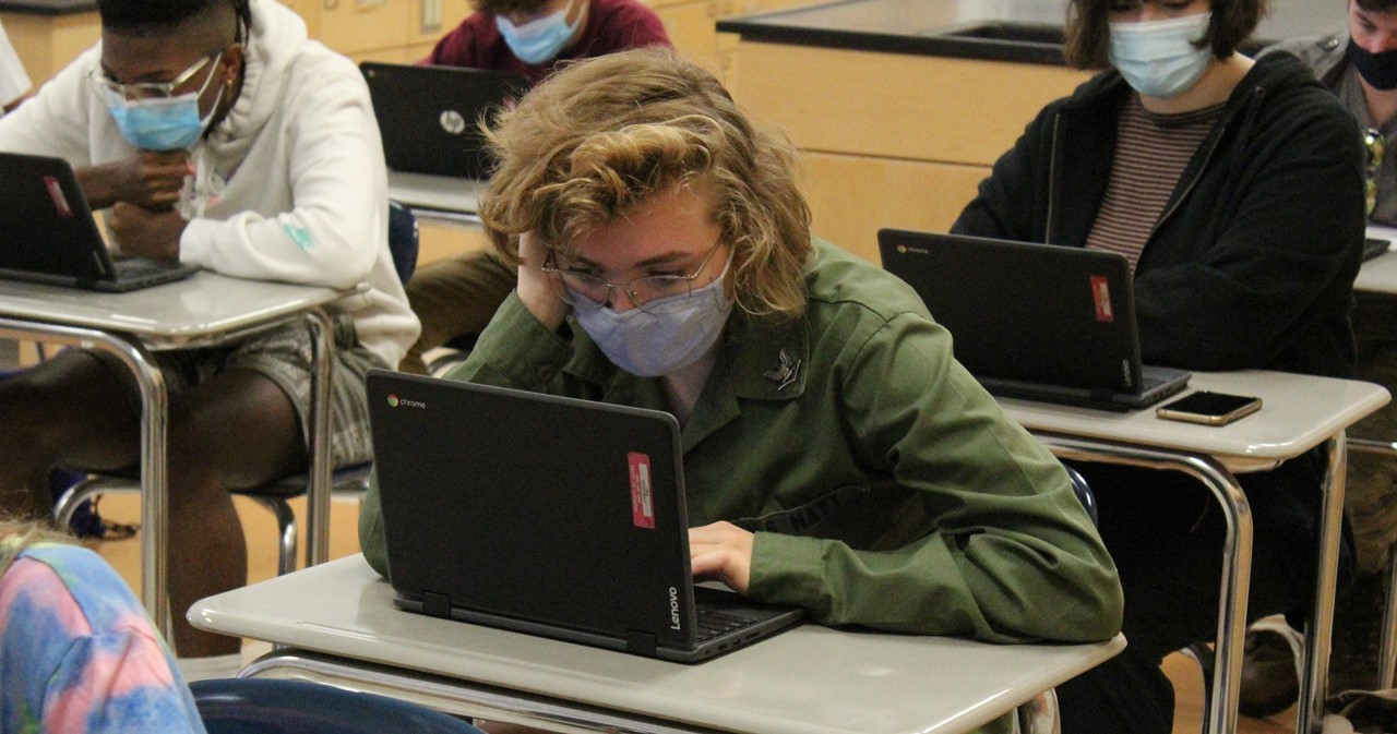Student at desk working on laptop